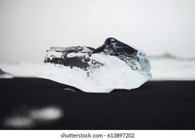 closeup of ice block on black Iceland sand