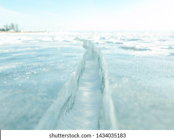 Close-up of ice crack of frozen lake Baikal surface in winter and white flake of ice in gap; the ice crevasse texture (selected focus).
