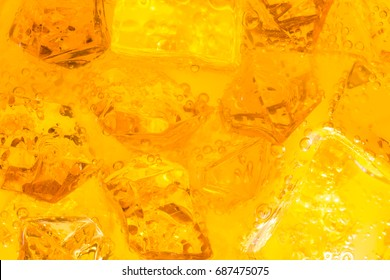 Close-up of ice cubes in drink or orange juice