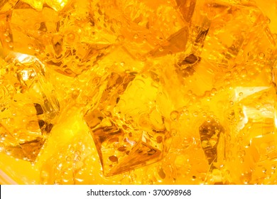 Close-up of ice cubes in orange juice