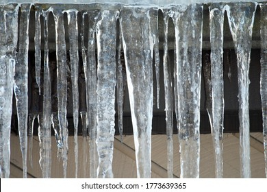 Closeup of icicles hanging off a roof in the sunlight