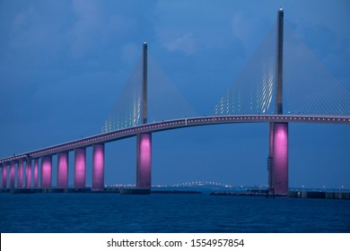 Closeup of the iconic Sunshine Skyway Bridge spanning the wide mouth of beautiful Tampa Bay in central Florida lit up in pink LED lights to commemorate Breast Cancer Awareness Month.