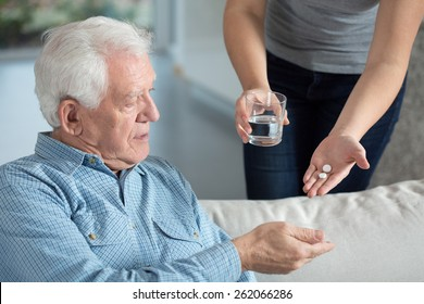 Close-up of ill senior man taking medicine