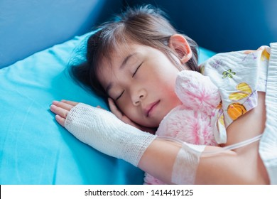 Closeup of illness asian child admitted in hospital with saline intravenous (IV) on hand. Girl sleeping at comfortable equipped hospital room. Health care stories.
