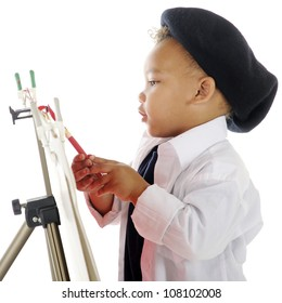Closeup image of an adorable preschool artist painting on an easel in his smock and French beret.  On a white background.