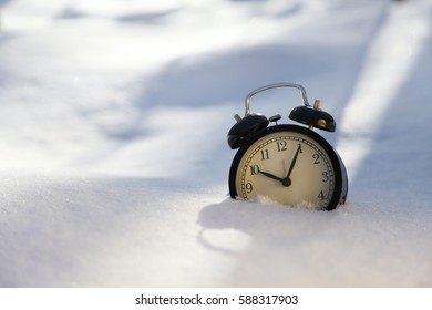 Closeup image of alarm clock in snow. Spring time concept image with copyspace