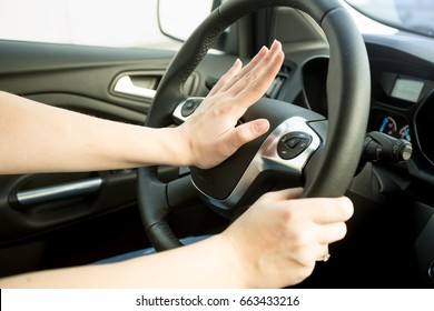 Closeup image of annoyed woman driving car and honking