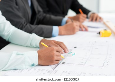 Close-up image of architects being occupied with paperwork