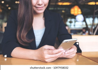 Closeup image of an asian businesswoman holding , using and looking at smart phone