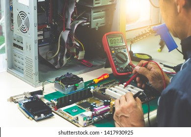 Closeup image of asian technician man hand measuring electrical voltage of computer mainboard by using digital multimeter. Maintenance  and repair computer hardware  service concept.