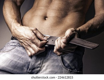 Closeup image of attractive young muscle man undoing belt, shirtless fashion male portrait wearing jeans, contrast studio, grunge fashion male portrait
