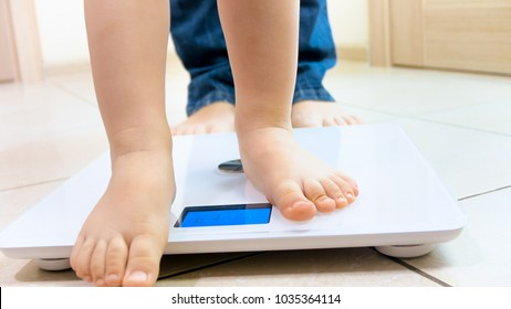 Closeup image of baby feet next to mothers standing on digital scales