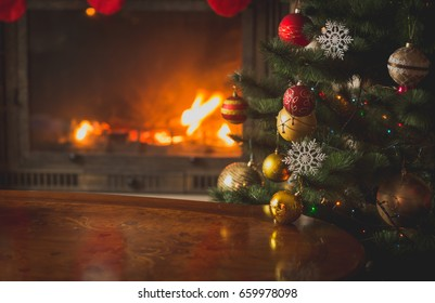 Closeup image of baubles on Christmas tree in front of burning fireplace. Beautiful Christmas background