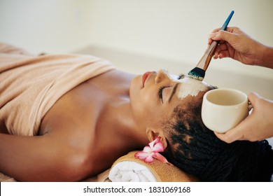 Close-up image of beautician applying deep clearing clay mask on face of Black young woman