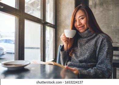 Closeup image of a beautiful asian woman reading a book while drinking coffee in cafe