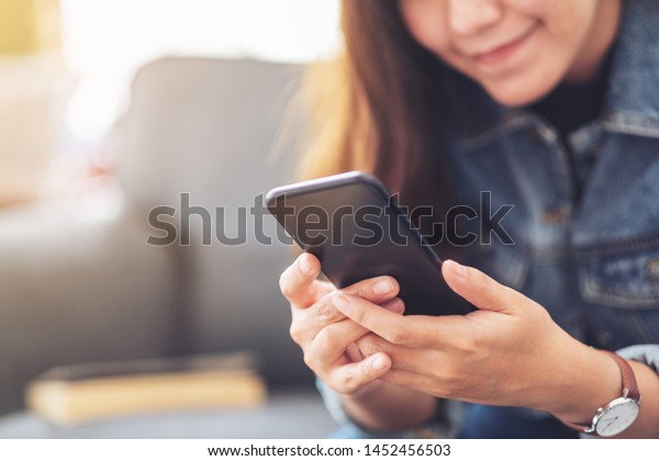 Closeup image of a beautiful asian woman holding , using and looking at smart phone