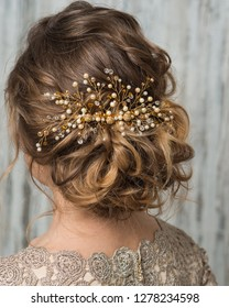 Close-up image of beautiful hairstyle decorated by gold shiny hair accessory, rear view
