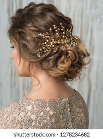 Close-up image of beautiful hairstyle decorated by gold pearl shiny hair accessory, rear view