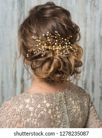 Close-up image of beautiful hairstyle decorated by gold beaded shiny hair accessory, rear view