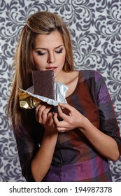 Close-up image of a beautiful lady eating bar of chocolates