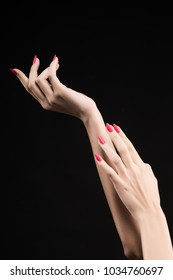 Closeup image of beautiful woman hands with pink manicure on the nails. Cream for palms, manicure and beauty treatment. Elegant and graceful arms with graceful fingers. Copy space. Isolated on black.