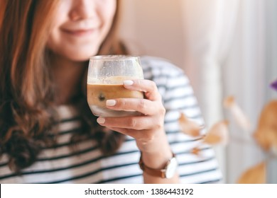Closeup image of a beautiful woman holding a glass of iced coffee to drink in cafe