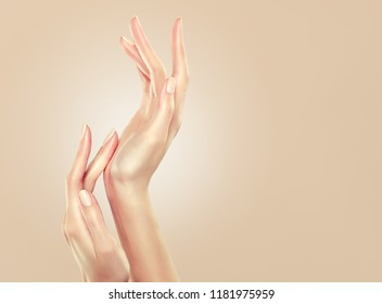 Closeup image of beautiful woman's hands with  light pink manicure on the nails. Cream , manicure and beauty treatment.  Elegant and graceful arm with slender graceful fingers. Skin care