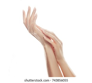 Closeup image of beautiful woman's hands with  light pink manicure on the nails. Cream for hands, manicure and beauty treatment.  Elegant and graceful hands with slender graceful fingers.