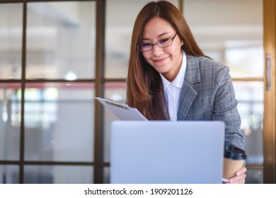 Closeup image of a beautiful young asian business woman drinking coffee and using laptop computer while working in office