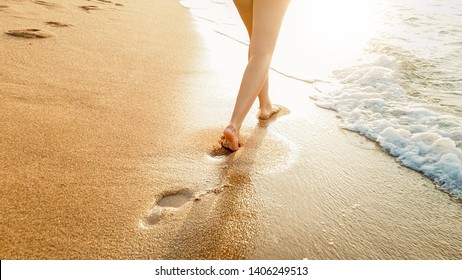 Closeup image of beautiful young barefoot woman walking in the calm warm sea waves against amazing sunset