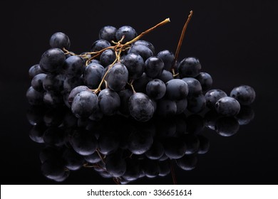 Closeup image of black grapes on black background with reflection