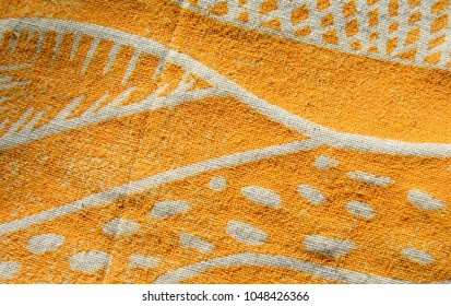 Closeup image of a bright yellow printed artwork on cotton fabric