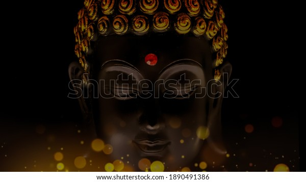 closeup image of  buddha in a calm meditative state with peaceful smile in his face.buddha idol face edited with Bokeh lights.