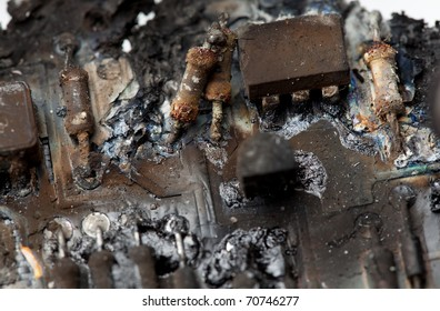 A close-up image of burnt components of a circuit board.  / BURNT CIRCUIT BOARD