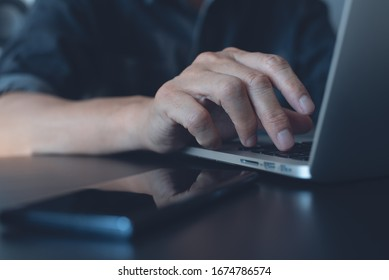 Closeup image of a business man's hands working and typing on laptop computer keyboard with mobile smart phone on wooden table, online working from home, portable office concept