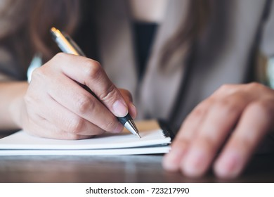 Closeup image of business woman writing on blank notebook on wooden table