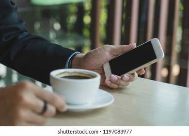 Closeup image of businessmen hands holding digital mobile with blank copy space screen for your text message or promotional content against desktop and coffee cup.
