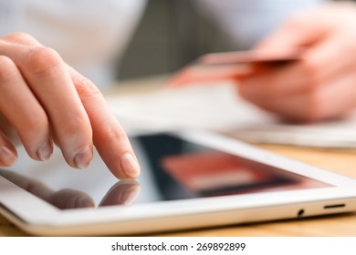 Closeup image of a businesswoman paying by credit card through a tablet computer with a touch screen.