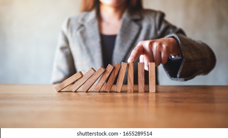 Closeup image of a businesswoman try to use finger to stop falling wooden dominoes blocks for business solution concept