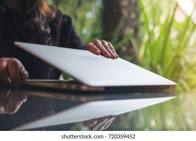 Closeup image of a businesswoman's hands close and open laptop on glass table in office with blur green nature background