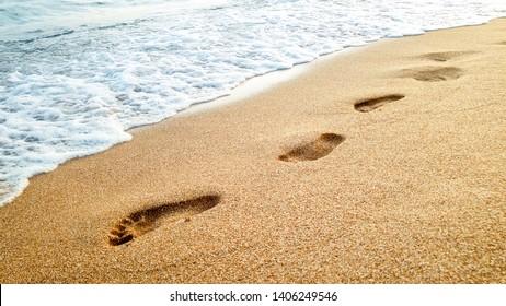 Closeup image of calm sea waves washing off human footprints on wet sand at sandy sea beach