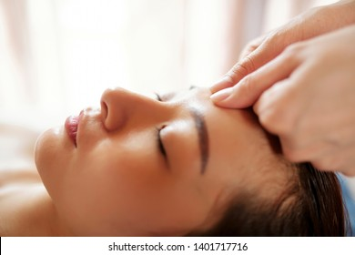 Close-up image of calm young Asian getting relaxing face massage with oils