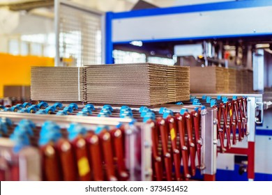 Closeup image of cardboard boxes on conveyor belt in distribution warehouse