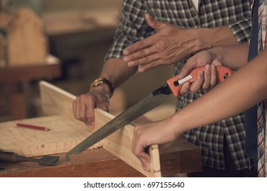 Close-up image of carpenter explaining his apprentice how to saw wood
