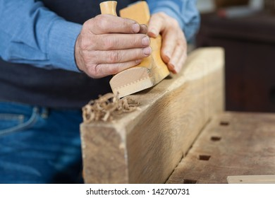 closeup image of a carpenter making something out of wood in the workshop.