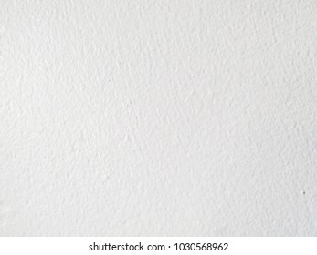 Close-up image of cement wall, painted white, rough surface.