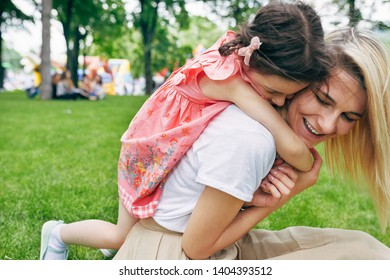 Closeup image of child embracing mother in the park. Pretty little girl piggybacks her young attractive mother sitting on green grass outside. Love emotion. Happy Mothers Day. Motherhood and childhood