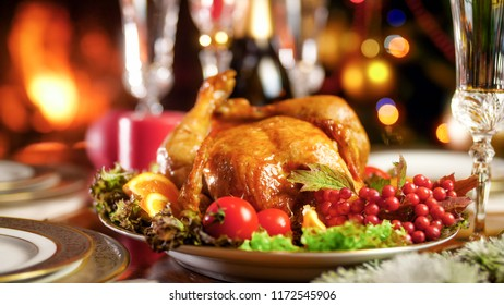 CLoseup image of Christmas dinner table with baked chicken against burning fireplace