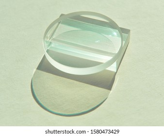 Closeup image of circular convex lens placed on top of clear rectangular acrylic prism, creating beautiful reflection and refraction image inside. Shade and shadow on white paper background
