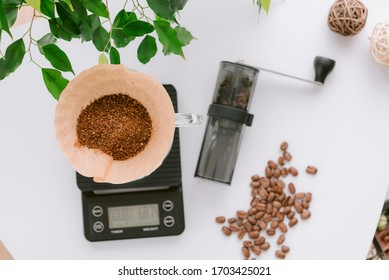 Closeup image of coffee grounds in paper filter on digital coffee scale while making a drip coffee with beans and coffee grinder on the table.